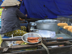 River Vendor Making a Barbecue Sandwich